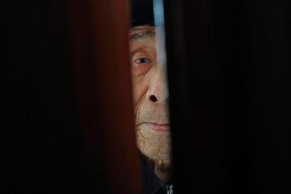 Старик смотрит в щель приоткрытой двери в китайском доме для престарелых